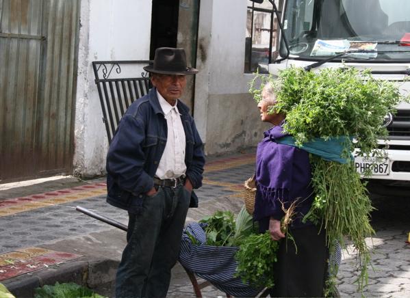 Tradition Ecuadorian man and women leaving the market in Otivollo